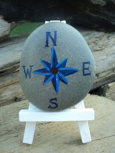 Compass rose in nautical motif hand painted on Lake Erie beach stone, bright and navy blue on 4 inch white easel.. $8.00, via Etsy.