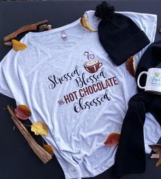 """Our """"Hot Chocolate Obsessed"""" flowy tee is perfect for you chocolate lovers out there! Featured on a heathered white dolman/flowy tee is super comfy and has a more loose fit."""