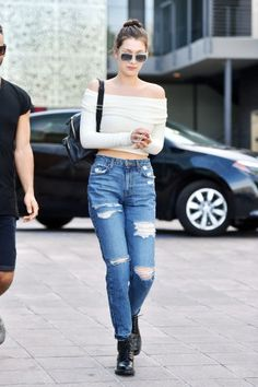 12 stylish ways to wear boyfriend jeans: Bella Hadid wears a ripped pair of boyfriend jeans with an off-the-shoulder shirt and booties
