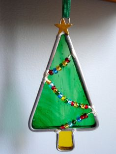 This little Christmas Tree measures 2.25 wide x 4.5 long and is made with green streaky translucent glass and decorated with colorful beads. It is