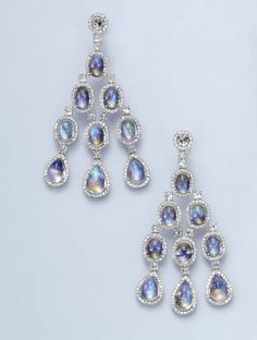 A PAIR OF MOONSTONE AND DIAMOND EAR PENDANTS   Each rose-cut diamond, within a circular-cut diamond surround, suspending a series of cabochon moonstone links, each with circular-cut diamond borders, spaced by rose-cut diamond links, mounted in 18k white gold