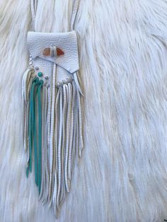 This beautifully hand crafted medicine pouch has been made and blessed for you to carry your special crystals and other treasures close to you with convince. White and turquoise leather medicine bag with tangerine quartz crystal closure. Tangerine quartz is an excellent stone to use when