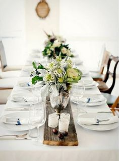 I like the formality of the white tablecloth with the informality of the salvaged wood runner, mismatched chairs and casual flower selection and arrangement.