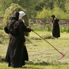 Romanian nuns - one looks to be a novice (white veil) - doing some yard or farm work