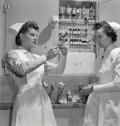 """November 1942. """"Nurses in training. Babies' Hospital, New York. A graduate nurse (right) watches student Susan Petty prepare a hypodermic for a patient. Strict adherence to doctors' orders is something every probationer must learn."""" Photo by Fritz Henle for the Office of War Information."""