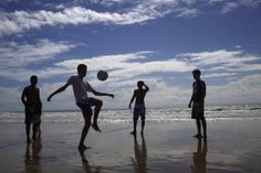 Residents and tourists play soccer on Ponta Negra beach in Natal, Brazil, Wednesday, June 25, 2014. Natal is one of many cities hosting the World Cup soccer tournament this month. (AP Photo/Hassan Ammar)