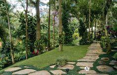 Gramado amplo e caminhos graciosos compõem o jardim - Casa