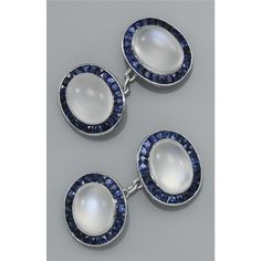 A PAIR OF SAPPHIRE AND MOONSTONE CUFFLINKS Centring on a cabochon moonstone bordered by French-cut sapphires
