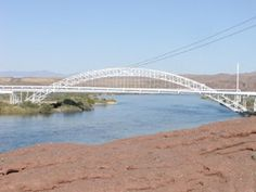 The Old Trails Bridge is south of I40 where it crosses the Colorado River at Topock, AZ.  To park and view the bridge, take the Interstate 40 exit for Park Moabi, the 1st Cal.exit from the east.  Follow the Park Moabi Entrance Rd. north to its intersection with the Natl Trls Hwy then turn right. The 1st vantage point is from an old brick bridge. Cont. past the first vantage point; then look for a historic concrete billboard and adjacent pullout pad.  That provides the best view of the…