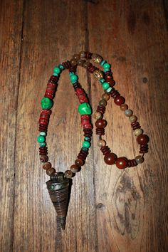 Necklace with red yak bone beads, green skulls, turquoise mala beads, boddhi seeds, mahogany red brown wood discs, coffee stripe agate beads & a tibetan conch shell pendant. 45 € (5)