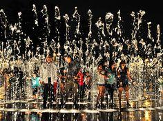 Imagem de pessoas em pé na fonte de um parque aquático no Peru