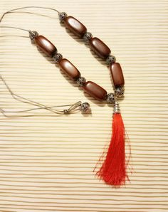 "Mahogany colored wooden beads and ornate silver beads pair with a 2.5"" tassel on…"