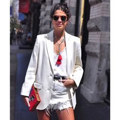 """Leandra: """"My clutch is by Olympia Le-Tan."""" I ran into Leandra earlier today carrying one of those brilliant story book clutches. She also got the memo on wearing all white/red accents.  #manrepeller #white #red #streetstyle #wheredidugetthat #denim #instastyle #olympialetan @manrepeller"""