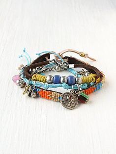 Set of three bead and charm embellished leather and knotted chord bracelets. Skinny leather bracelet has lobster claw clasp closure, knotted chord bracelet has adjustable pull closure, and wider beaded leather bracelet has tie closure. A spectacular arrangement of color of and design to showcase on your wrist.                                                    *Leather, Acrylic, Base Metal