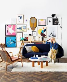 This colourful Scandi style living room with herringbone parquetry flooring features a striking gallery wall of artworks | Photography: Alicia Taylor | Styling: Kerrie-Ann Jones