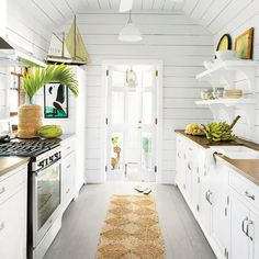 Wall and ceiling paneling in Touch of Grey by Devoe Paint makes this small cottage kitchen airy and bright. Beachy touches such as a grass runner, model sailboat, and ipe countertops add coastal flair to the charming galley-style space.