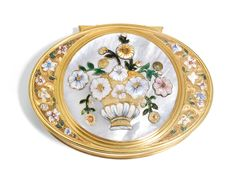 A gold and enamel snuff box, probably English, circa 1735 -- oval with extended hinge, the lid spandrels chased and enamelled with trailing flowers on a textured ground, the lid inset with a later mother of pearl panel applied with a fantastical chinoiserie vase of matching enameled flowers, apparently unmarked 7.5cm., 3in. wide