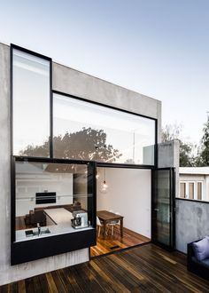"""Again I like the the """"over sized"""" windows and dark edges to them that make them stand out from the grey building. I like the open living arrangement and easy flow between the interior and exterior.  I also like the idea of having an outdoor patio."""