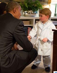 Barack Obama and First Lady Michelle crouch down to meet and shake hands with Prince George at Kensington Palace