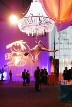 Aerial Bartenders or 'Champagne Chandeliers' make a unique and stunning addition to any wedding!  This act consists of (2) 30 Minute or (3) 20 minute set performances in which our performer is hanging (upside down!) from the ceiling above your guests, from a beautiful chandelier. While suspended from the chandelier, she dances spectacular choreography and pours flutes of champagne at the same time!  You may prefer freshly made cocktails.