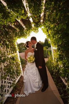 Bride and Grooms First Look, and First Kiss under the archway entry into Stonebrooks Gardens. Weddings at Stonebrook Manor Event Center and Gardens in Thornton, Colorado.