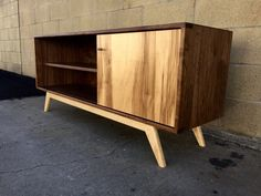 A mid century modern credenza great for a TV or record player and records. Has a great contrast with a mixture of walnut and maple. Hand applied