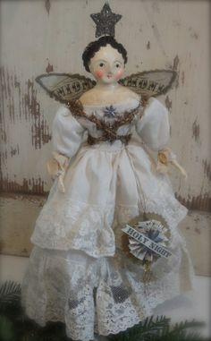 """By Nicole Sayre.  The Angel of the Holy Night is  dressed in a lace-trimmed cotton gown made from the leg of pantalets from a theatre costume from the 1920's. Her trim is antique tinsel & dresden stars.  Her wings & ornament are fashioned of paper with glitter accents. She is papier mache on a cloth body & comes with her own stand 12"""""""