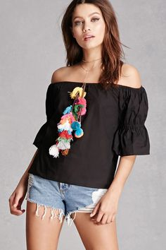 A woven blouse featuring an elasticized off-the-shoulder neckline with a multicolor tassel pom pom detail, and 3/4 length sleeves with elasticized ruffle cuffs.  This is an independent brand and not a Forever 21 branded item.