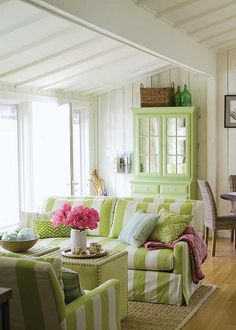 cottage living room in green. stripes of leaf green and butterscotch yellow in compliment. pink flower showpiece as room decor. all such colors adds brightness to the space.