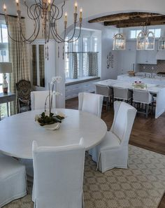 Love this Coastal French interior kitchen and dining area. Beautiful rough saw beamed ceiling against crisp white interior! Interior Design Ideas
