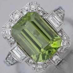 Art Deco Peridot Diamond Ring Platinum ring with a prong-set 4.96ct emerald-cut peridot, flanked by bezel-set emerald-cut diamond shoulders, and surrounded by further diamonds