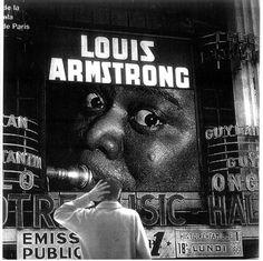 Julio Cortázar ante un cartel del trompetista y cantante estadounidense Louis Armstrong.