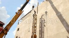 Large crane lifts a long concrete pile vertically and lowers it into place in a yellow steel pile driving frame /  One of many Construction, Demolition, Dredging, and Building clips