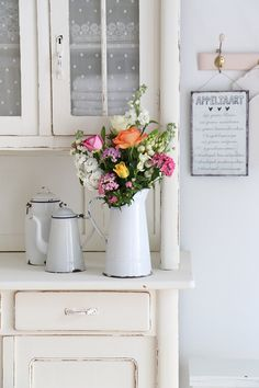 fresh bouquet in chippy enamelware, and a distressed painted cupboard on a pretty blog