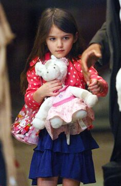 Suri Cruise's Best Fashion Moments, So Far At only 7, this little lady has donned more darling outfits than most of us could count in kindergarten. . . . Steal the Spotlight - Spotted:  Cuteness overload!  Looking like she jumped straight out of a Crew Cuts catalogue, the 5-year-old throws a classic polka-dot cardigan over a ruffled frock and makes the grown-up style age-appropriate with a plastic Hello Kitty bag.