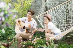 a couple is smiling each other playing the guitar in a park