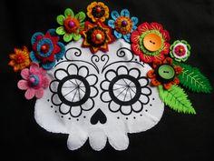 Catrina pintada a mano decorando flores de fieltro de varios colores cosidas todas a mano es la decoración de una bolsa de tela.