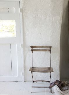 A chair by the door. Plaster walls. Natural light.