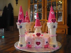 Princess Castle Cake - normal round cake with butter cream icing and the towers are made with ice cream cones dipped in melted chocolate and rolled in crystal suger.