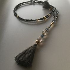 Long Collier en Y en perles de rocaille, quartz fumé et pompon de soie matteCouleur dégradé de gris et orLongueur approximative: 50 cmPIECE UNIQUE