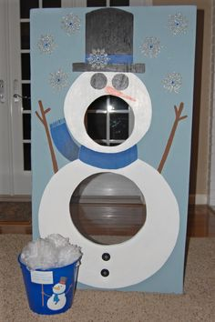 """Snowman bean bag toss with bucket of """"snowballs"""" (white shower loofahs from the Dollar Tree)."""