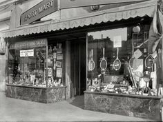 """Washington, D.C., 1923. """"Sport Mart, 1410 New York Avenue N.W."""" Continuing our day of window-shopping. National Photo glass negative. It's so cool to see this photo in a larger form to look into the windows and see all the 1920's ads and sporting equipment"""