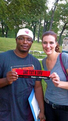 Street Team members Leroy and Ruthy showing off Hupy and Abraham 'DNT TXT N DRV' bumper stickers at COA Youth & Family Centers Skyline Music Series in Kadish Park.