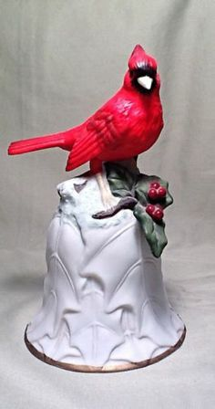 cardinal in flight, carrying an antique porcelain bell