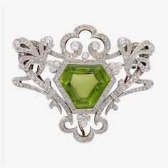 A Belle Époque peridot, diamond and platinum-topped eighteen karat gold pendant brooch  centering a modified shield-shaped peridot in a detailed rose, single and old mine-cut diamond surround.