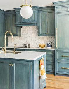 These blue-green cabinets have an aged, hand-brushed look set against white countertops and backsplash and adorned with shiny brass cabinet hardware.