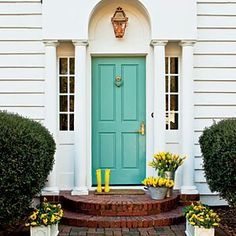 Turquoise front door looks pretty with the pop of bright yellow