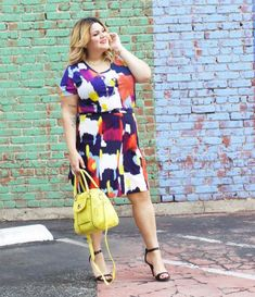 A multi-colored dress is cinched at the waist with a thin belt and paired with yellow purse and black heels.