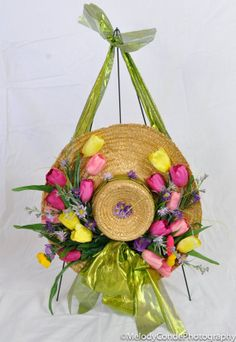 Beautiful Easter Straw-hat with artificial silk Tulips on brim and a green bow and sash for hanging.  Perfect for Easter!  Can hang on door for a lovely display.  Hat is approx. 17 inches round.