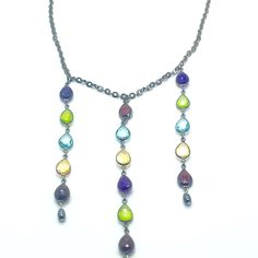 "Elizabethan is a 15"" Necklace with 3 Linear Drops of Semi Precious Stones: Garnet, Peridot, Citrine, Aqua-Marine, and Amethyst on Sterling Silver Chain with Black Rhodium Plating. Each Drop Ends with a Hematite Rice Bead. Drops are two at 4"" each, and center one at 4 1/2"". The Chain is Oxidized Sterling Silver with a Lobster Claw Clasp. Each Stone Measures 7/16"" x 5/16"" and are Fully Rounded on Front and Back. Product #14-091"